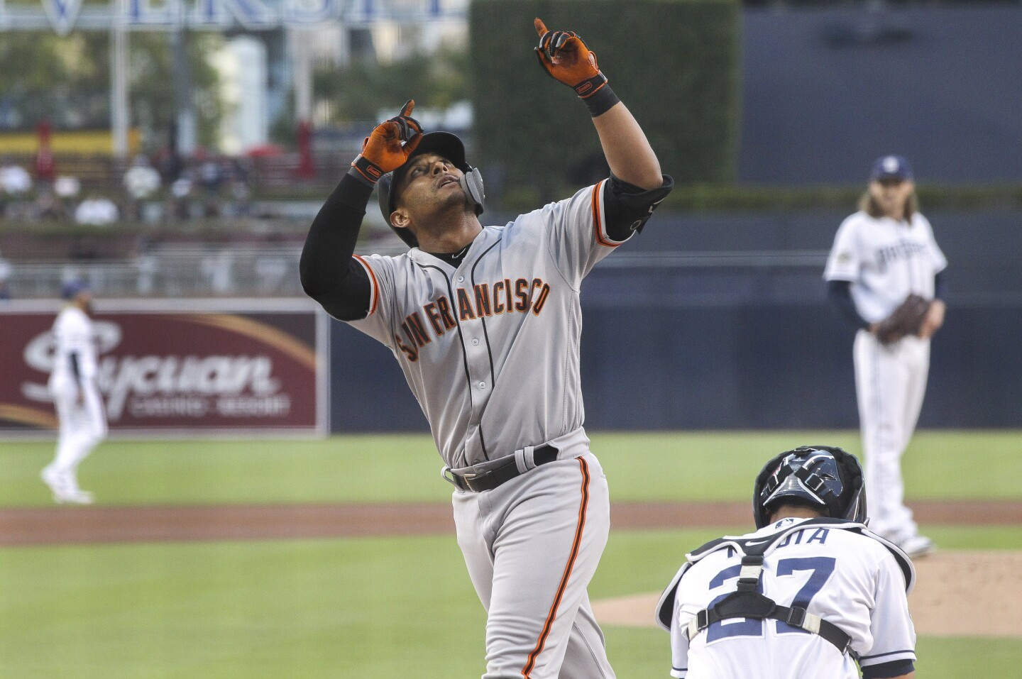 The Giants' Donovan Solano points up after hitting a home run off of Padres' pitcher Matt Strahm, right, in the first inning at Petco Park on Tuesday, July 2, 2019 in San Diego, California.