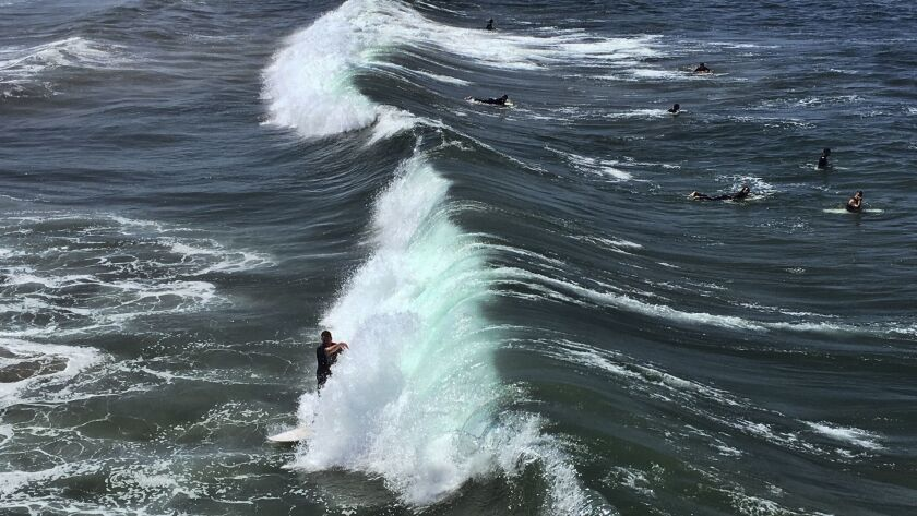 In this Sunday, June 10, 2018 photo a surfer catches a wave in Manhattan Beach, Calif. Southern Cali