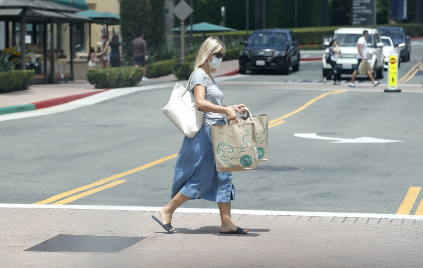 A shopper leaves Whole Foods in Fashion Island on first day of the latest shutdown of business.