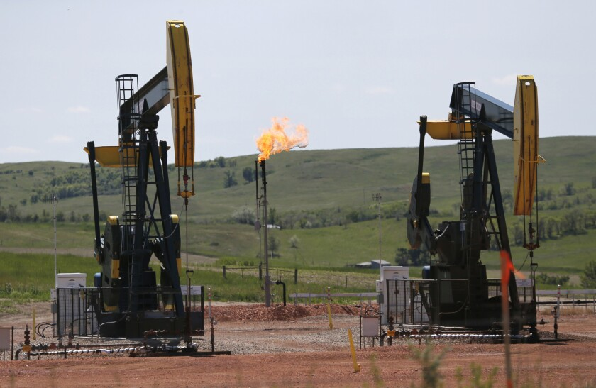 In this June 12, 2014 file photo, oil pumps and natural gas burn off in Watford City, N.D.