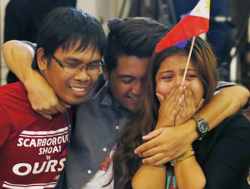 Filipinos celebrate the Hague-based U.N. international arbitration tribunal's ruling favoring the Philippines in its case against China on the dispute on South China Sea Tuesday, July 12, 2016 in the financial district of Makati city, east of Manila, Philippines. (AP Photo/Bullit Marquez)