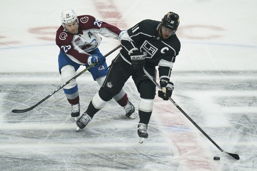 Kings center Anze Kopitar is defended by Colorado's Nathan MacKinnon on Jan. 21 at Staples Center.