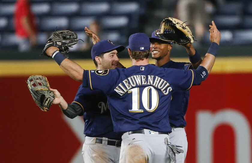 Milwaukee Brewers outfielders Ryan Braun, left, Kirk Nieuwenhuis (10) and Keon Broxton celebrate after the Brewers defeated the Atlanta Braves 3-2 in 13 innings in a baseball game Wednesday night, May 25, 2016, in Atlanta. (AP Photo/John Bazemore)