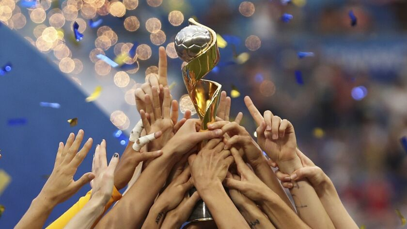 The United States players hold the trophy celebrating at the end of the Women's World Cup final socc
