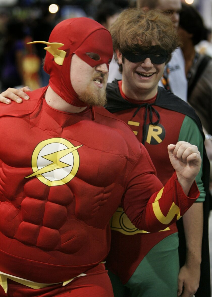 Dressed up as comic book super heroes, Dave Child, left, from Boston, Mass. as The Flash and Mickey Bloom, right, from Minneapolis, Minn. as Robin from Batman strut their stuff at the San Diego Comic-Con International Convention in the San Diego Convention Center.