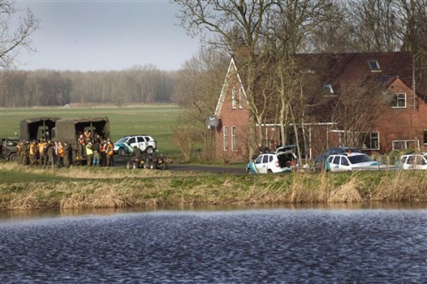 Police and military personnel gather in Woltersum, 200 kilometers (125 miles) north of Amsterdam, Friday, Jan. 6, 2012. Police and military personnel evacuated 800 people from four villages in the low-lying northern Netherlands on Friday amid fears of a dike break following days of drenching rains. (AP Photo/Harry Tielman)