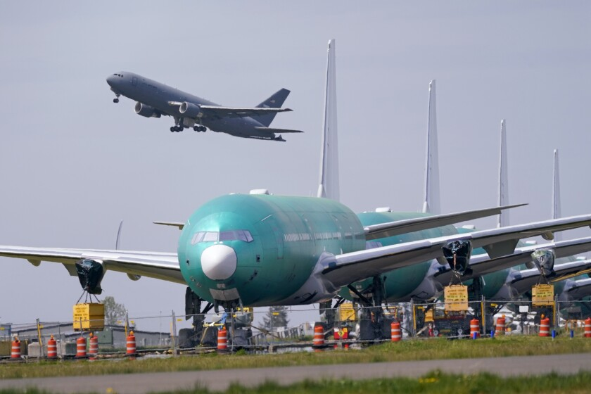 In this April 23, 2021 photo, a U.S. Air Force KC-46A Pegasus jet takes off in view of a line of Boeing 777X jets parked nose to tail on an unused runway at Paine Field, near Boeing's massive production facility in Everett, Wash. Orders to U.S. factories for big-ticket manufactured goods rose for the 12th time in the last 13 months in May, pulled up by a surge in demand for civilian aircraft.(AP Photo/Elaine Thompson)