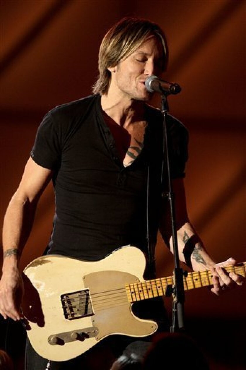 FILE - In this Nov. 9, 2011 file photo, country singer Keith Urban performs during the 45th Annual CMA Awards in Nashville, Tenn. Urban returned to the stage during The Grand Ole Opry on Friday, Feb. 3, 2012, his first public appearance since he had vocal surgery to remove a polyp from a vocal cord last November. He played three songs and an encore. (AP Photo/Mark Humphrey, file)
