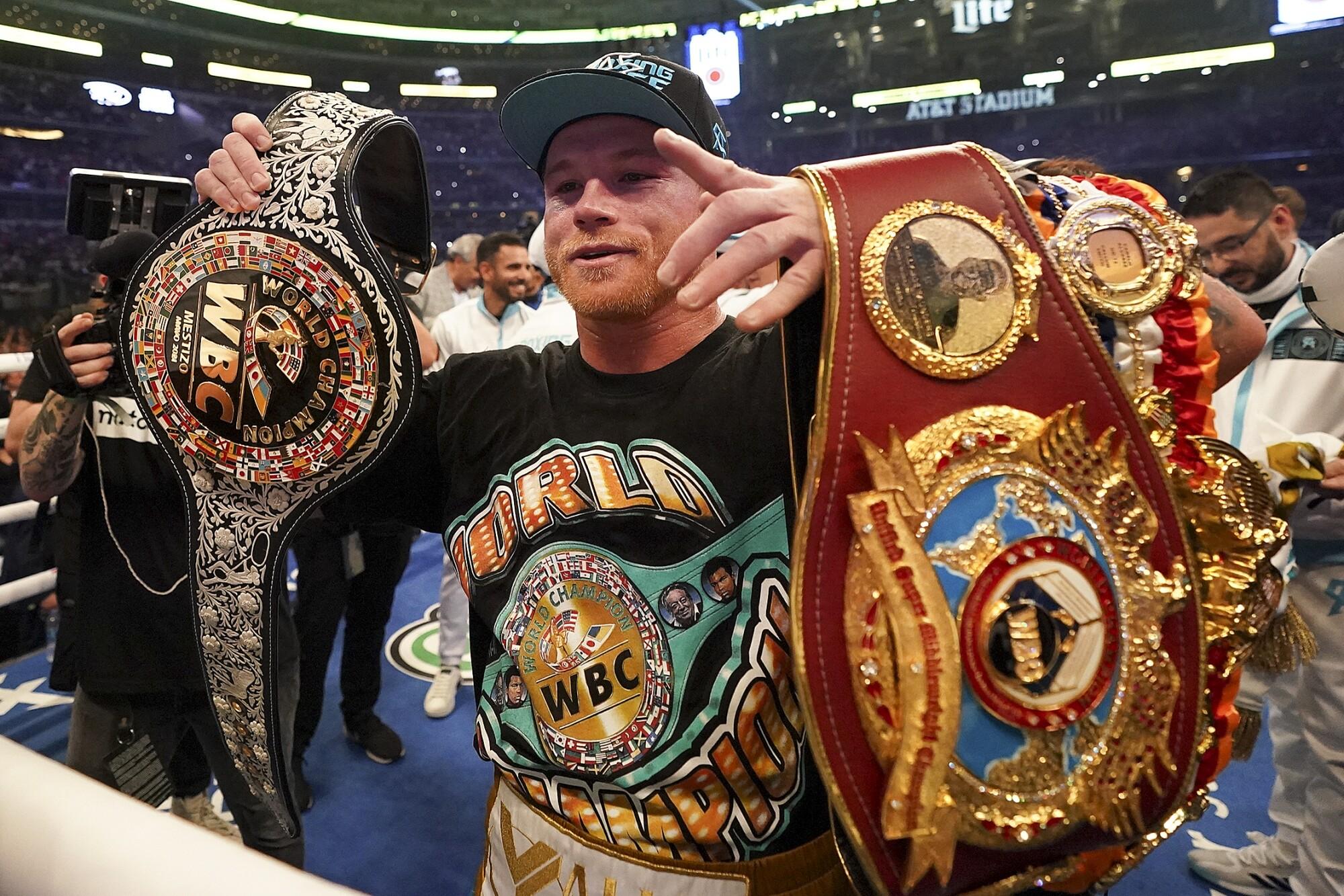 Canelo Álvarez celebrates with title belts after defeating Billy Joe Saunders.