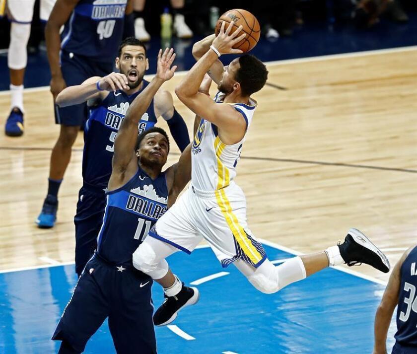 El jugador Stephen Curry (d) de Golden State Warriors intenta un lanzamiento ante Yogi Ferrell (i) de Dallas Mavericks, durante un juego entre Golden State Warriors y Dallas Mavericks de la NBA, que se disputa en el American Airlines Center, en Dallas, Texas (Estados Unidos). EFE