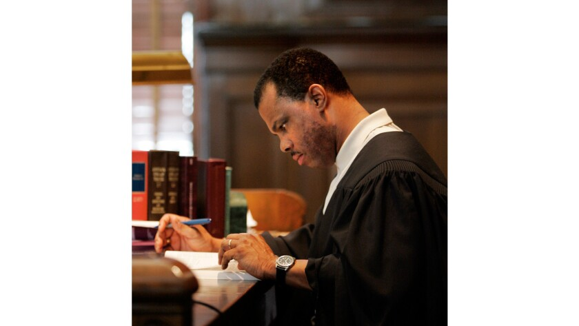 Judge Arthur L. Hunter reads court documents following hearings at Orleans Parish Criminal District Court in New Orleans May 23, 2007.