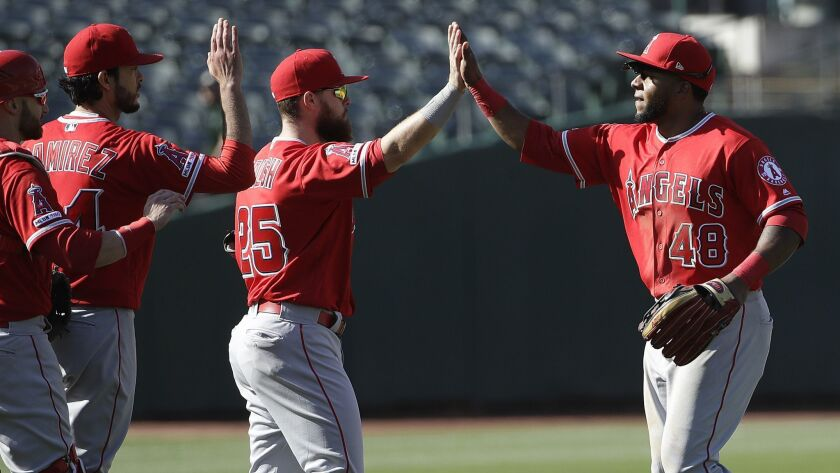 Angels' Cesar Puello, right, celebrates with teammates after defeating the Oakland Athletics in Oakland on Wednesday.