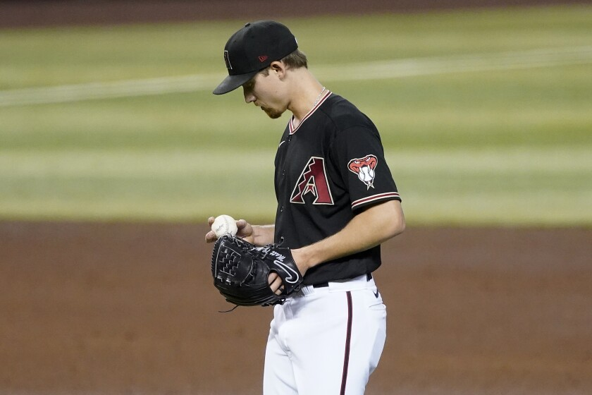 Arizona Diamondbacks starting pitcher Luke Weaver looks at the baseball after giving up a home run to the Colorado Rockies during the fourth inning of a baseball game, Saturday, Sept. 26, 2020, in Phoenix. (AP Photo/Matt York)