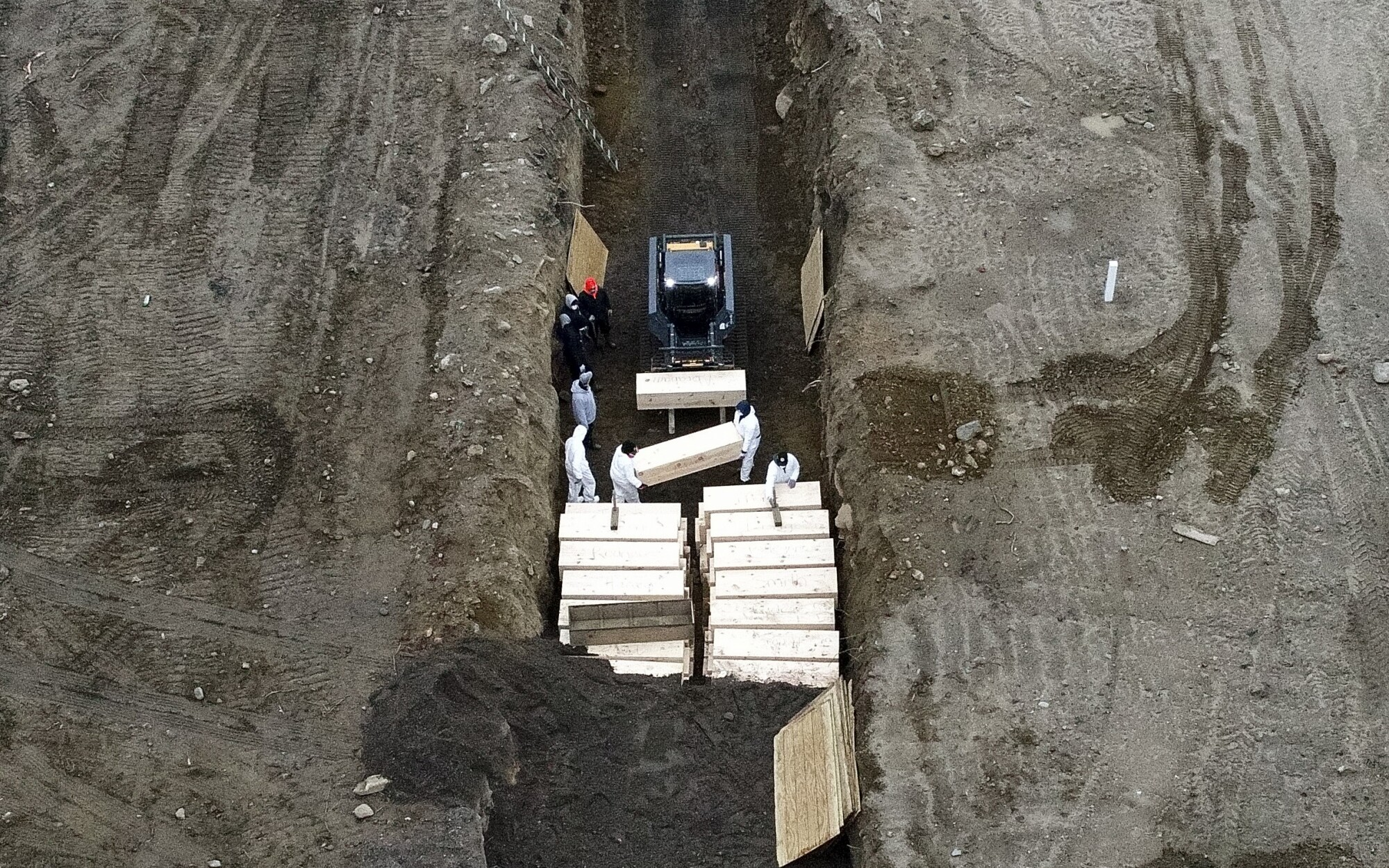 Workers bury bodies in a trench on New York City's Hart Island