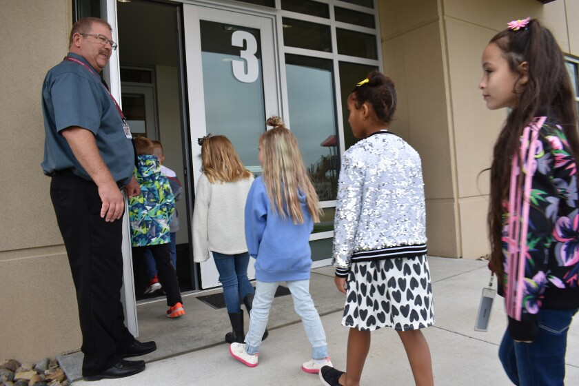 Principal Brad Foss holds the door for students returning from recess at Fox Hills Elementary School, Aug. 26, 2021, in Watford City, N.D., part of McKenzie County, the fastest-growing county in the U.S. School enrollment tripled over the past decade and is expected to double again by 2030, as McKenzie County became the fastest growing county in the U.S. (AP Photo/Matthew Brown)