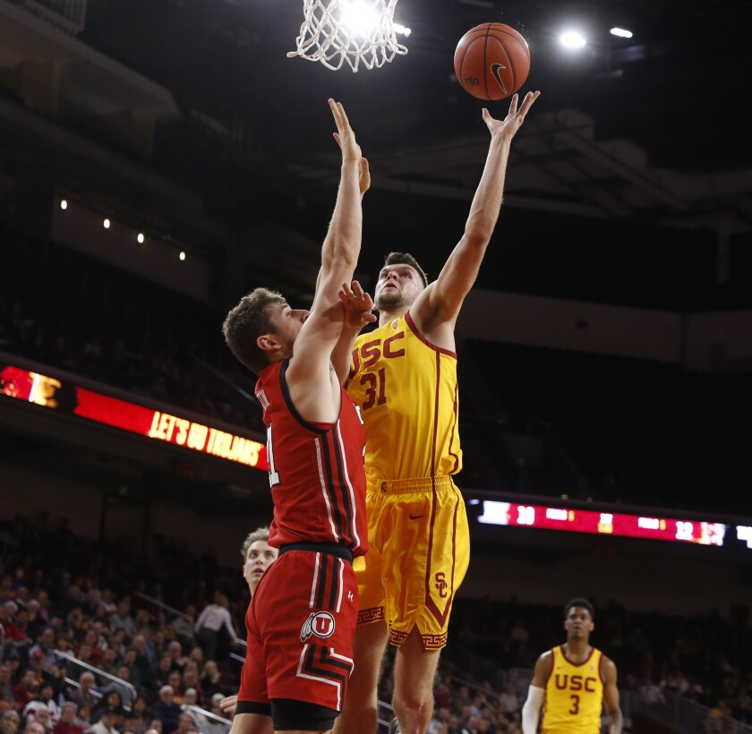 USC forward Nick Rakocevic (31) scores a basket guarded by Utah Utes forward Riley Battin (21) in the first half at the Galen Center on Thursday.