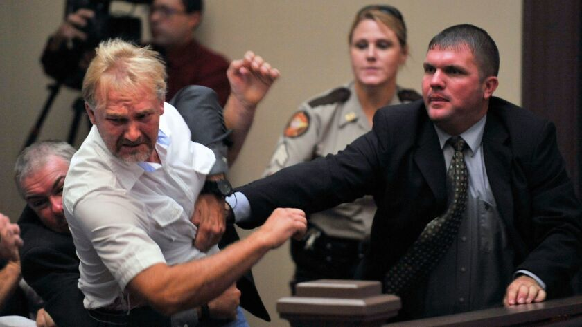 Wesley Thomas, the step father of Tiffany York, is tackled by courtroom security during the hearing