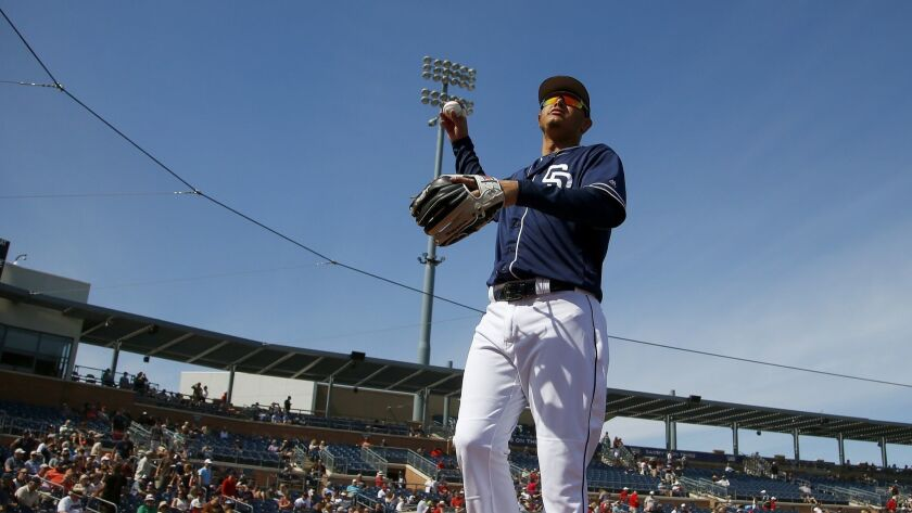 San Diego Padres' Manny Machado looks for a fan to throw a baseball to prior a spring training baseb
