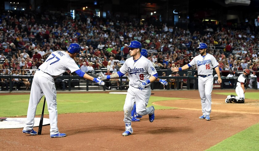 Dodgers' Yasmani Grandal (9) celebrates with pitcher Carlos Frias (77) after hitting a two-run home run against the Arizona Diamondbacks on Tuesday.