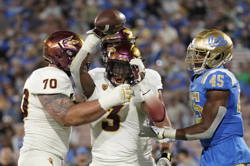 Arizona State running back Rachaad White, center, celebrates a touchdown along with offensive lineman Henry Hattis, left, as UCLA linebacker Mitchell Agude stands by during the second half of an NCAA college football game Saturday, Oct. 2, 2021, in Pasadena, Calif. Arizona State won 42-23. (AP Photo/Mark J. Terrill)