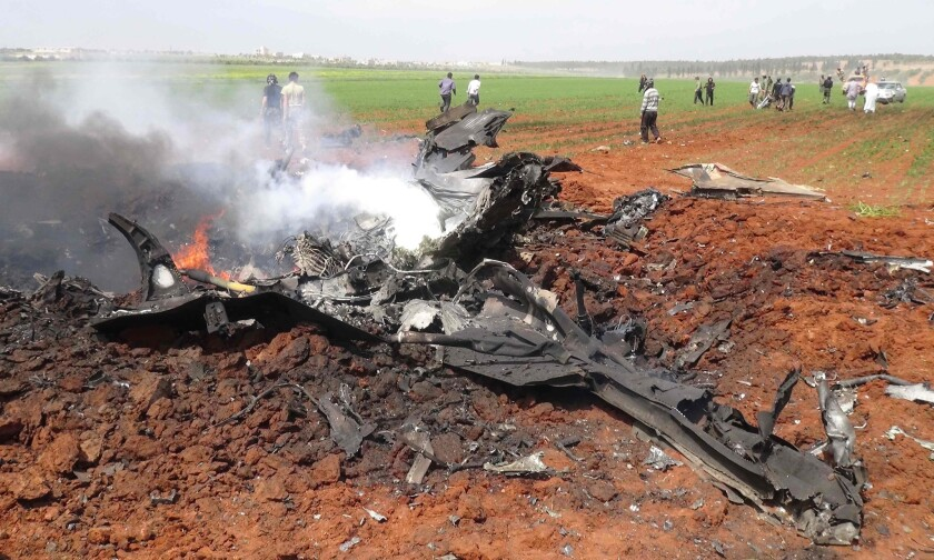 The wreckage of a government warplane burns after it was shot down by rebels over the northern Syrian town of Al Eis.
