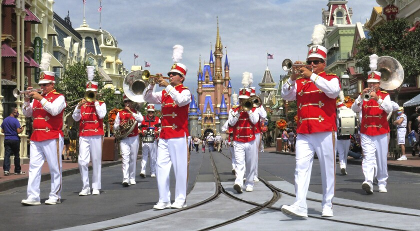 The Main Street Philharmonic marching band performs in the Magic Kingdom at Walt Disney World, in Lake Buena Vista, Fla., Wednesday, Sept. 30, 2020. The Walt Disney Co. announced Tuesday that it is planning to lay off 28,000 workers in its theme parks division in California and Florida. The company has been squeezed by limits on attendance at its parks and other restrictions due to the pandemic. (Joe Burbank/Orlando Sentinel via AP)