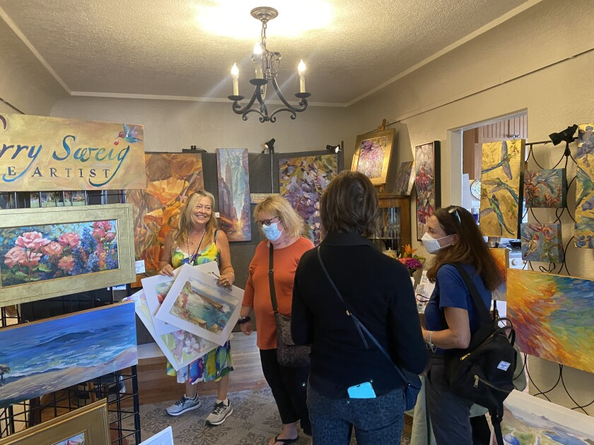 La Jolla painter Cherry Sweig (left) shows off her art to visitors as they tour the San Diego Coastal Art Studios on September 18.