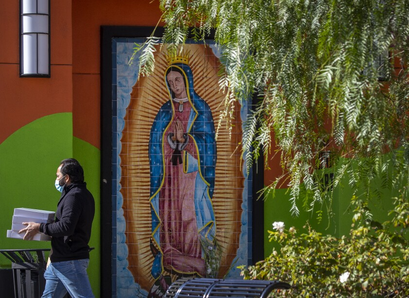 A man carries boxes of baked goods and passes by a mural of Our Lady of Guadalupe in downtown Santa Ana on Wednesday.