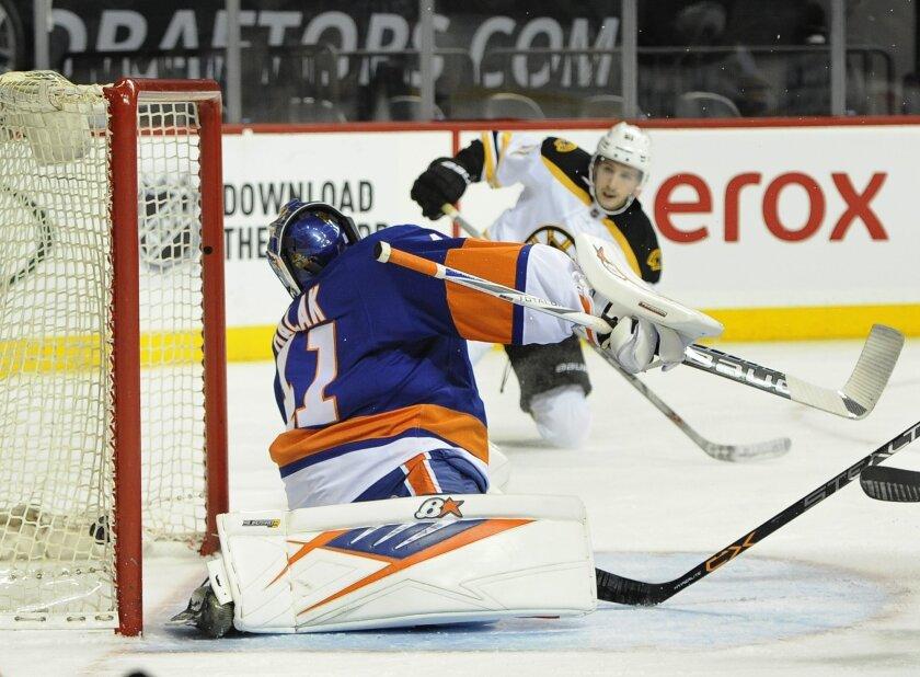 Boston Bruins' Ryan Spooner shoots the puck past New York Islanders goalie Jaroslav Halak (41) to score during the first period of an NHL hockey game on Sunday, Nov. 8, 2015, in New York. (AP Photo/Kathy Kmonicek)