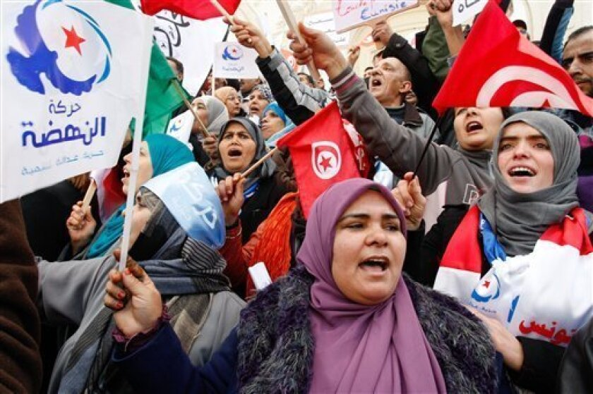 Supporter of the Islamist ruling party Ennahda,  hold Tunisian and party flags during a rally in Tunis, Tunisia, Saturday, Feb. 16, 2013. Activists from Tunisia's ruling Islamist party Ennahda denounce in a protest the plans for a government of technocrats  to solve the country's crisis. (AP Photo/