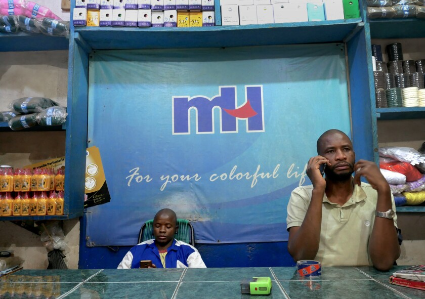 Trader Ibrahim Traoré talks on the phone in his shop in Dabanani market in central Bamako, Mali on M
