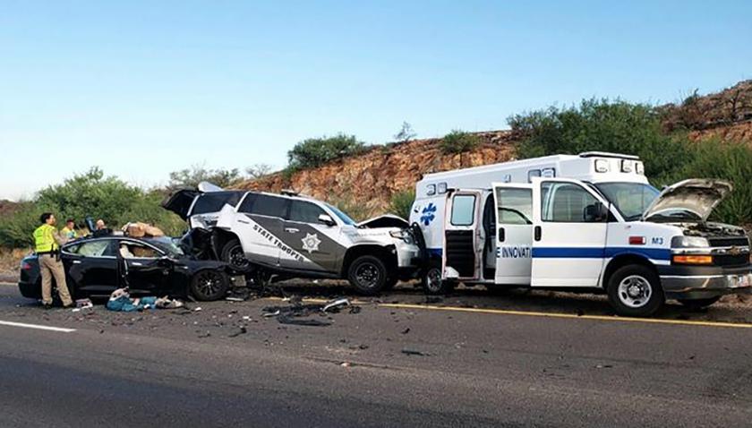A crash scene involving a Tesla, a police vehicle and an ambulance.