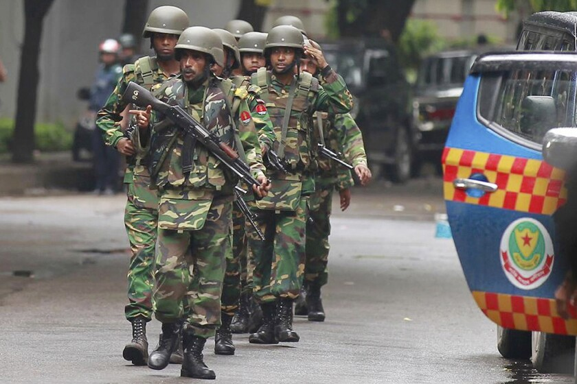 Bangladeshi soldiers walk through the area in the capital, Dhaka, where armed militants attacked the Holey Artisan Bakery.