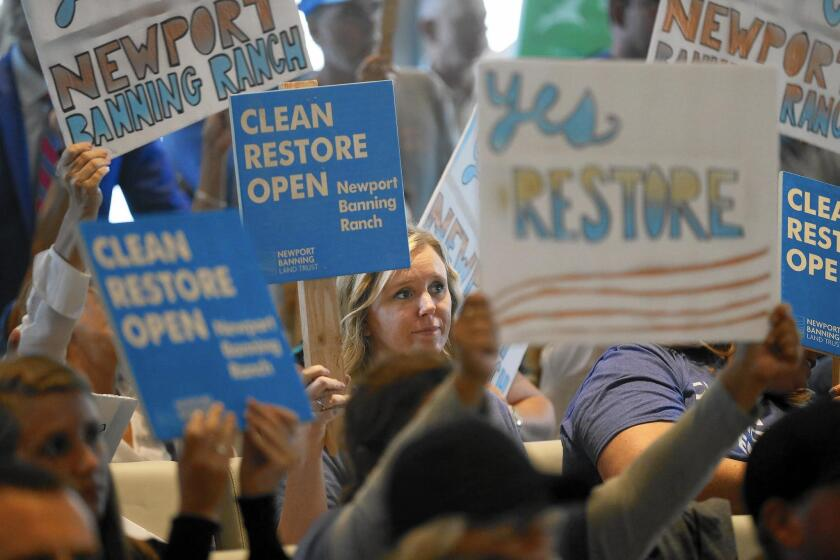 Supporters of the proposed Banning Ranch development project show their sentiments at the California Coastal Commission's hearing Wednesday in Newport Beach.