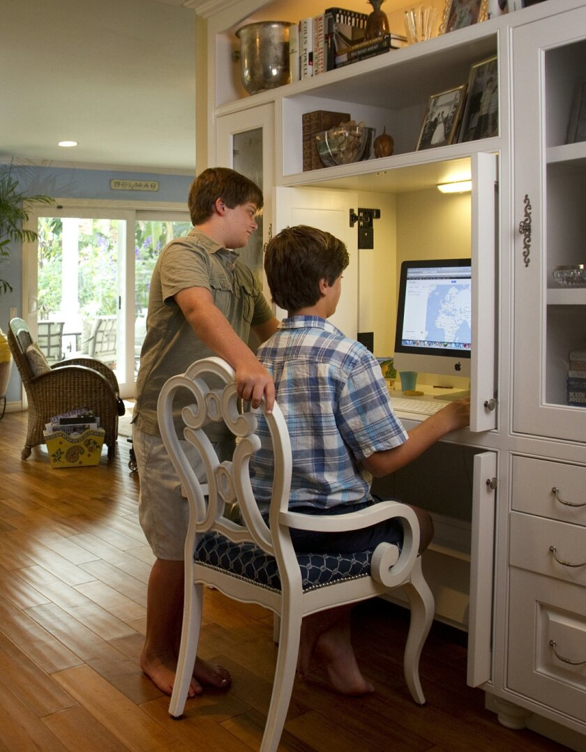 Brothers Jack and Max Rosoff work on the computer at a built-in desk located near the kitchen.