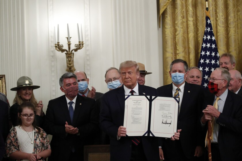 "President Donald Trump poses for a photo during a signing ceremony for H.R. 1957 – ""The Great American Outdoors Act,"" in the East Room of the White House, Tuesday, Aug. 4, 2020, in Washington. (AP Photo/Alex Brandon)"