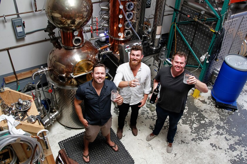 Distillers (from left) Whit Rigali , Blake Carver, and Sam Chereskin toast their Misadventure Vodka on Friday at California Spirits Company in San Marcos, California.