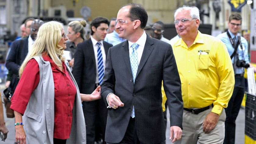 U.S. Labor Secretary Alexander Acosta, center, tours a plant in Detroit on June 1. He is expected to be asked Wednesday about Trump's proposal.