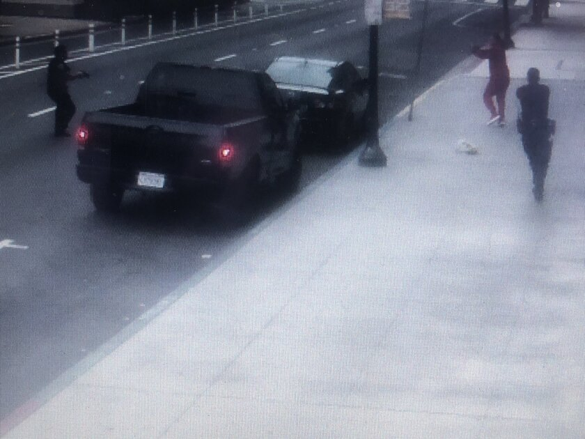 Two officers with parked cars between them point guns at a man who appears to be turning toward them with his arm raised