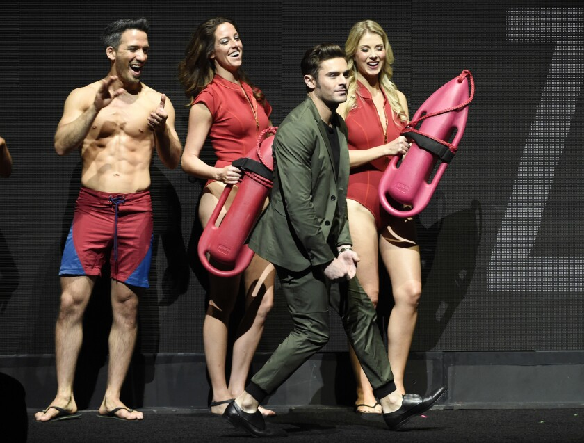 "Zac Efron, a cast member in ""Baywatch,"" walks past models dressed as lifeguards as he is introduced to the crowd during the Paramount Pictures presentation at CinemaCon 2017 at Caesars Palace on March 28.sday."