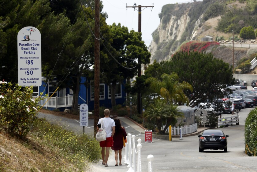 A couple who parked their car on Pacific Coast Highway walk toward Paradise Cove hoping to avoid paying the $35 daily parking fee in Malibu.