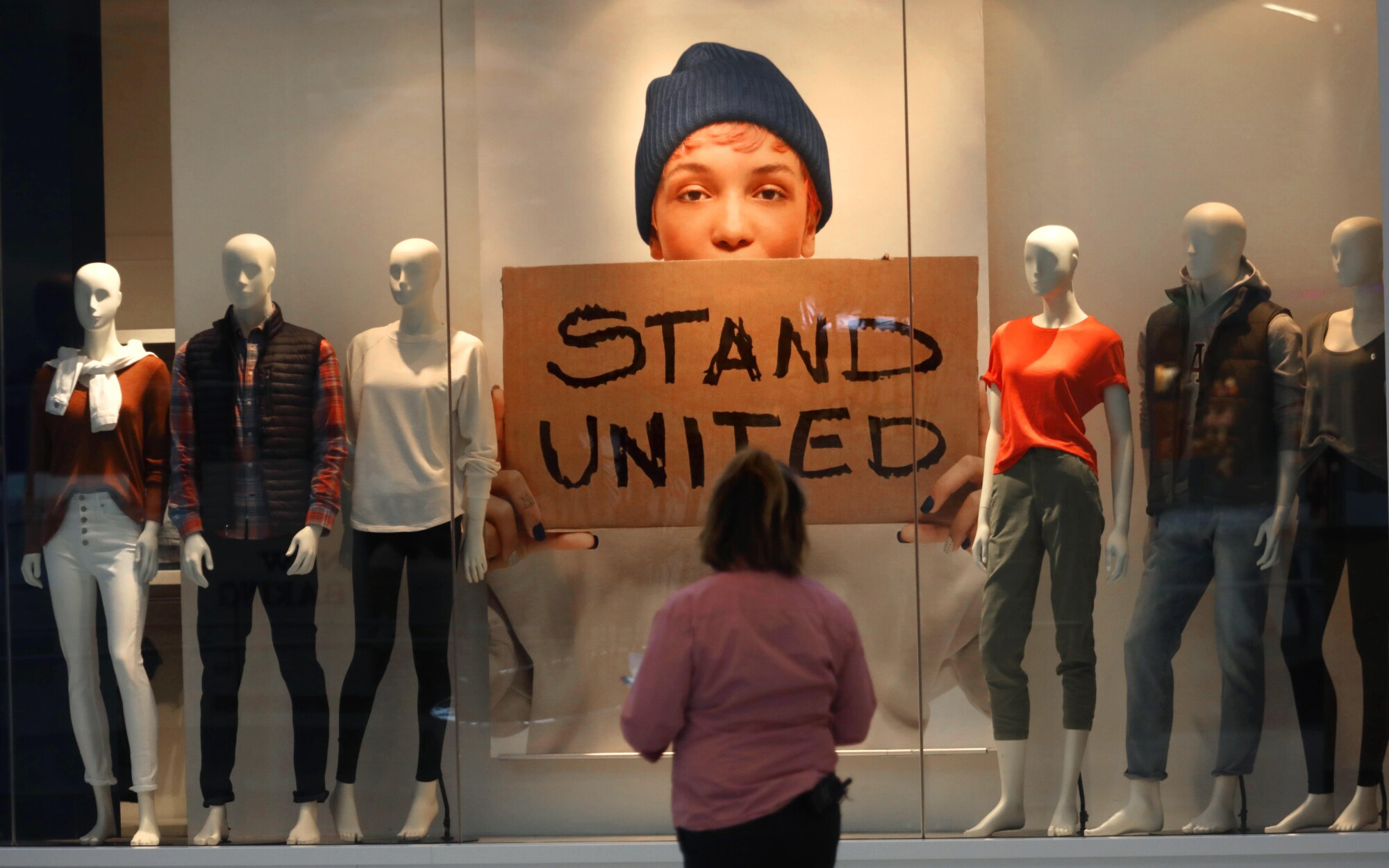 "A woman looks at a window display including a sign saying ""Stand United."""