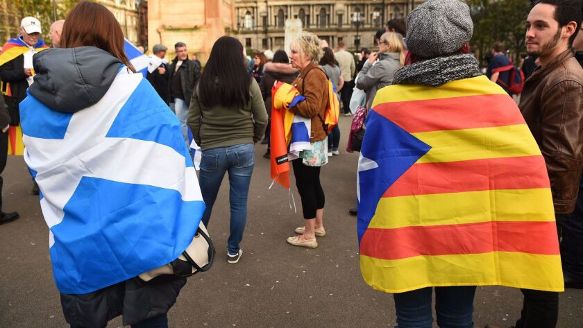 Demonstrators wear the flag of Scotland and the Catalan flag during a demonstration to show solidarity with Catalonia in central Glasgow on Oct. 9.
