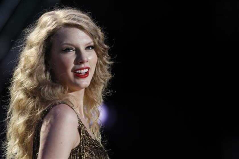 In this Sunday, June 12, 2011, file photo, Taylor Swift performs during the CMA Fan Fest in Nashville, Tenn. For the first time in her career, Swift had to postpone her Saturday, July 2, 2011, sold-out show at the Yum Center in Louisville under doctor's orders due to illness. (AP Photo/Wade Payne, File)