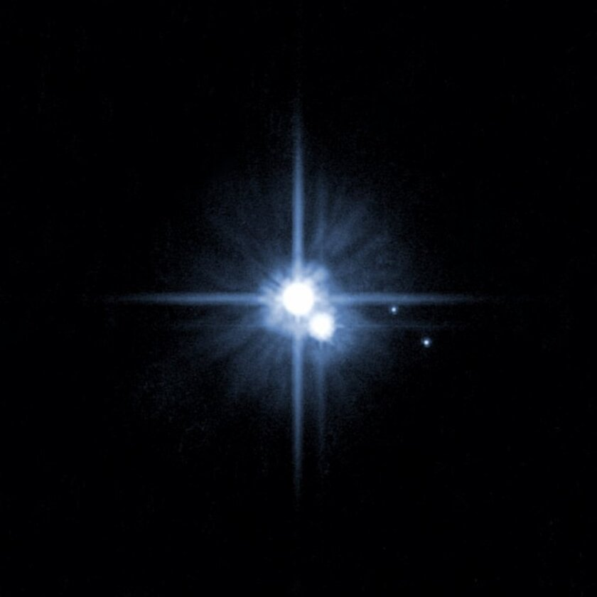 This image taken by the Hubble Space Telescope shows Pluto, center, with moons Charon, Nix and Hydra. Astronomers are asking the public to vote on names for two smaller moons, currently known as P4 and P5.