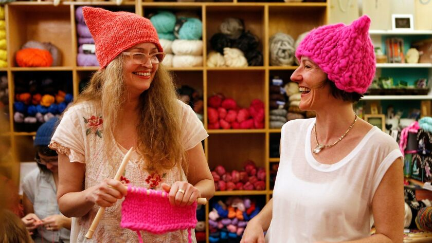 """Kat Coyle, left, owner of the Little Knittery in Atwater Village, shares a laugh with Megan Hollingshead, while teaching her how to knit a """"pussyhat"""" like the ones they are wearing."""