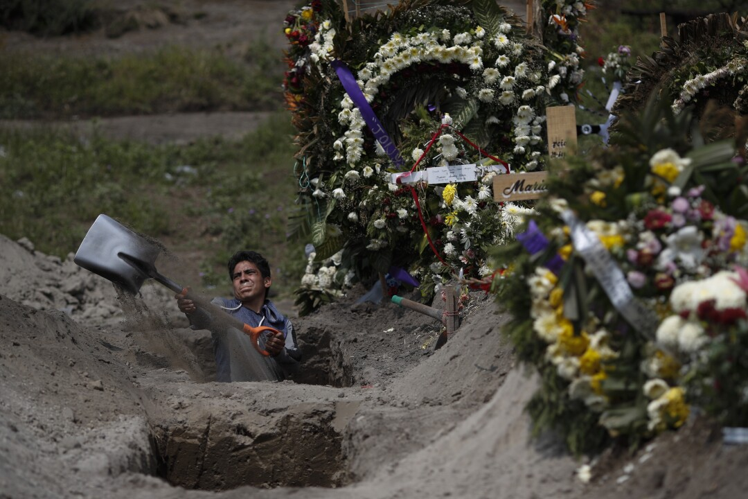 A cemetery worker digs a grave in Mexico City
