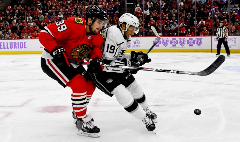 KKings left wing Alex Iafallo (19) tries to fend off Blackhawks defenseman Dennis Gilbert in a battle for possession of the puck during the first period on Oct. 27, 2019, in Chicago.