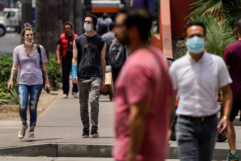 People wear masks, some only partially, in downtown Los Angeles on June 25.