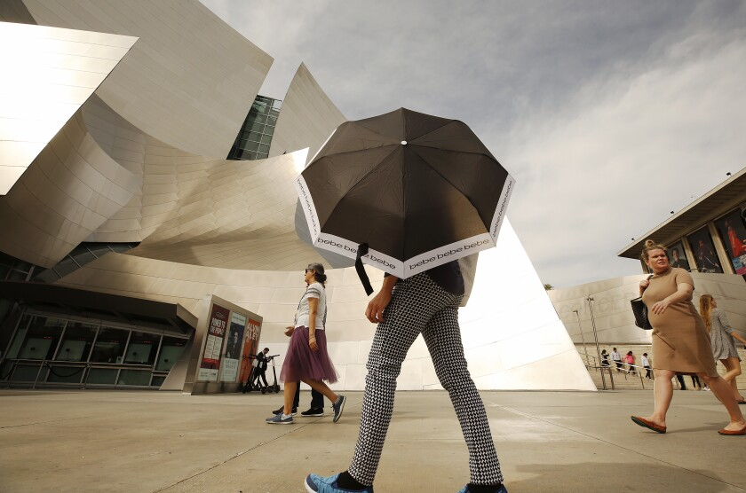 It was sunny and hot enough to need shade protection in downtown Los Angeles on Thursday. Record-setting heat will give way to cooler temperatures and the possibility of showers as a storm system moves over the Los Angeles area this weekend, forecasters say.